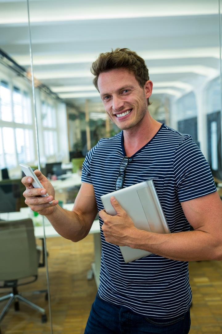Portrait of business executive using mobile phone in office