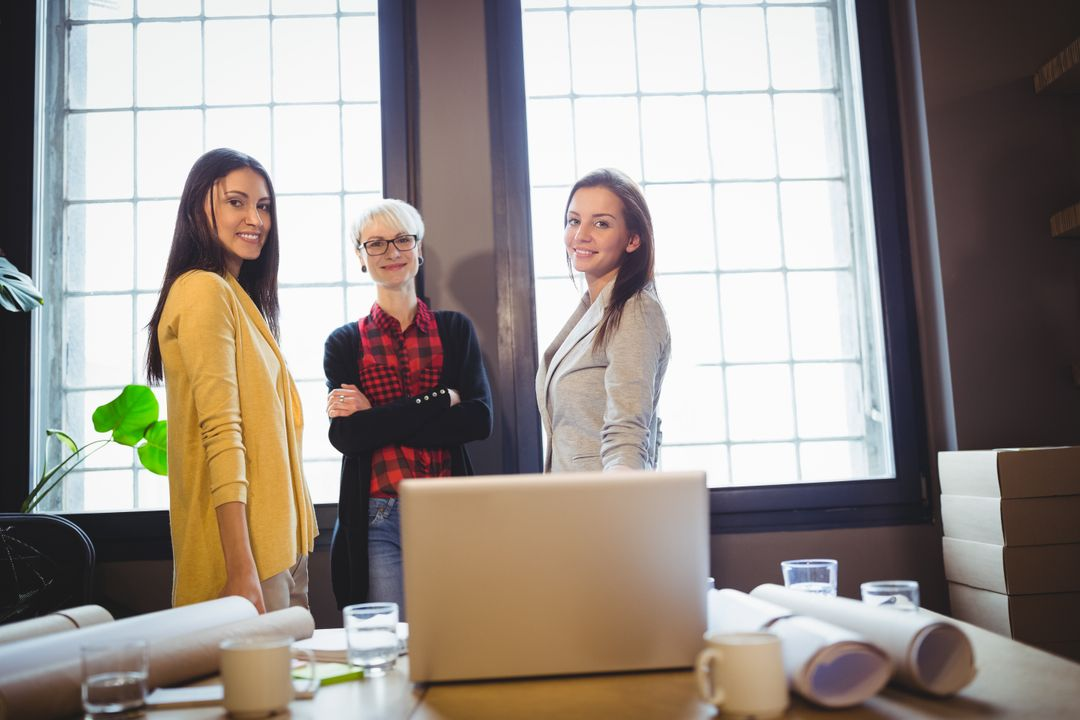 Portrait of confident female coworkers standing by desk in creative office Free Stock Images from PikWizard