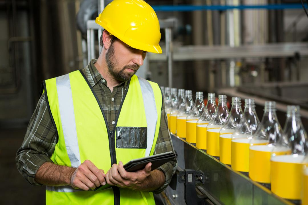 Serious male worker using digital tablet in juice factory
