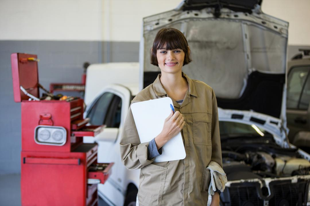 Female mechanic smiling at camera and holding clipboard at the repair garage