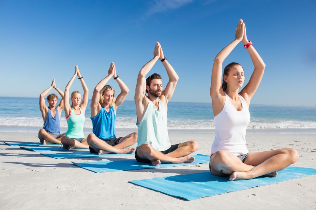 People doing yoga on the beach on a sunny day Free Stock Images from PikWizard