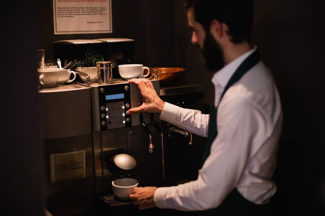 Waiter making cup of coffee from espresso machine in bar