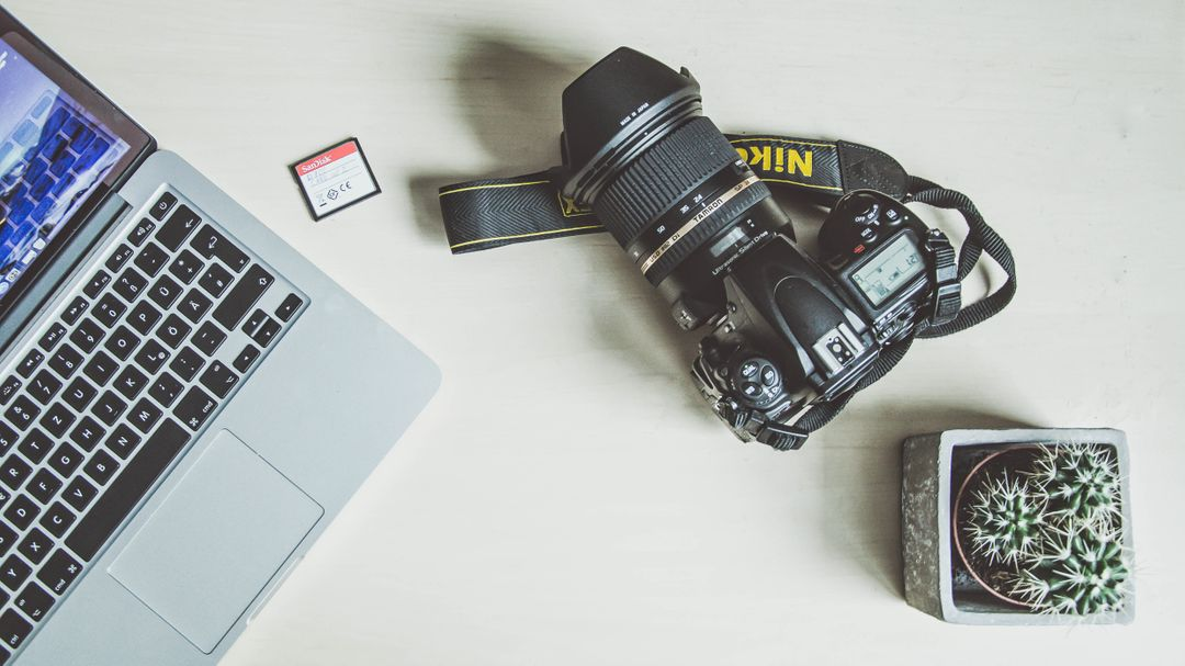Overhead image of a laptop, sd card, camera and a cactus plant on a wooden desk
