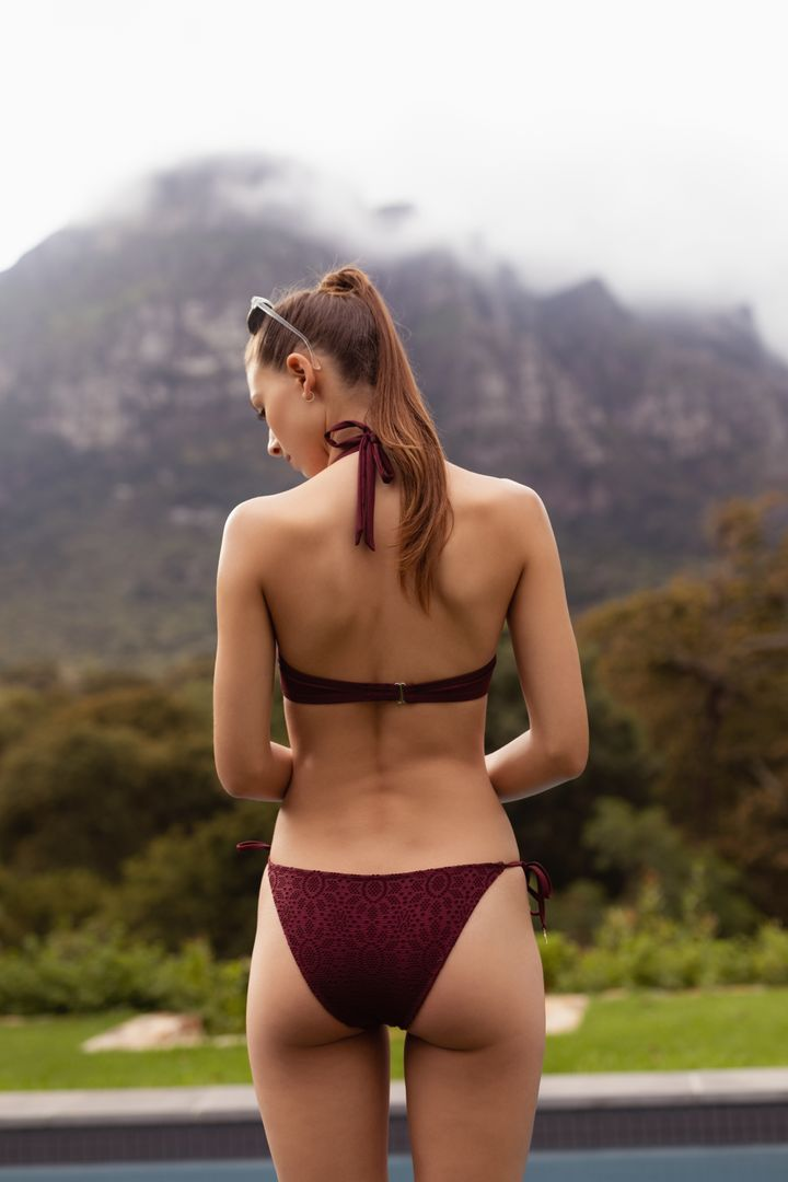 Rear view of woman in bikini standing near poolside in the backyard