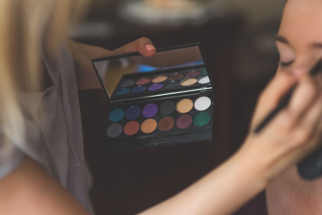 Image of a woman getting her makeup done, with applier holding an eyeshadow palette thats in focus