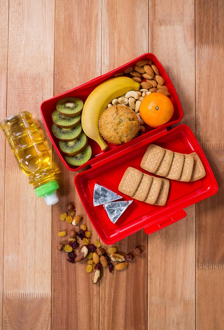 Various snack, fruit and oil arranged on wooden table