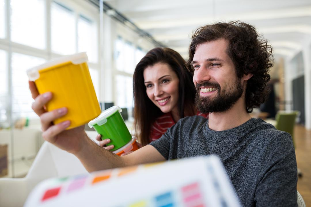 Male and female graphic designers holding plastic container in office Free Stock Images from PikWizard