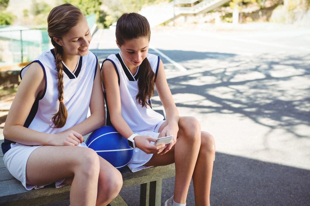 Female basketball players looking at smart phone while sitting on picnic table in court