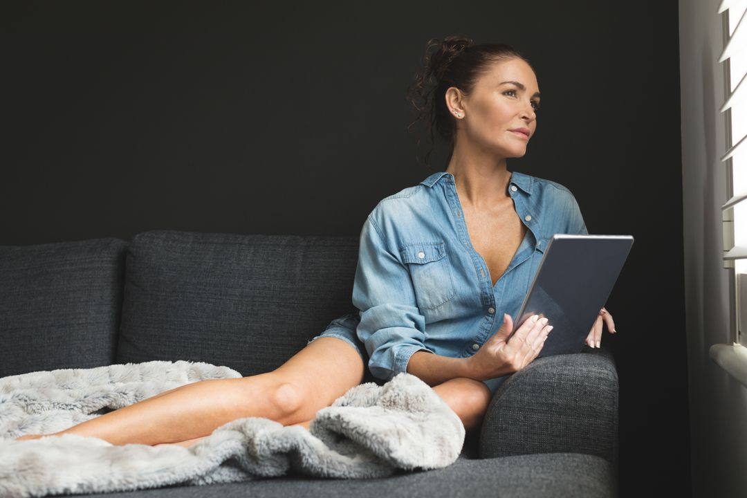Beautiful woman looking through window while using digital tablet on sofa in a comfortable home
