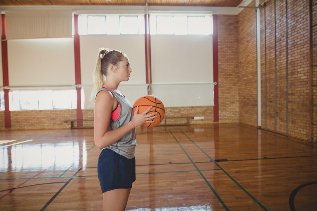 Determined high school girl standing with basketball in the court Free Stock Images from PikWizard