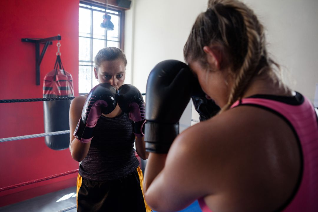 Trainer assisting woman in boxing at fitness studio Free Stock Images from PikWizard