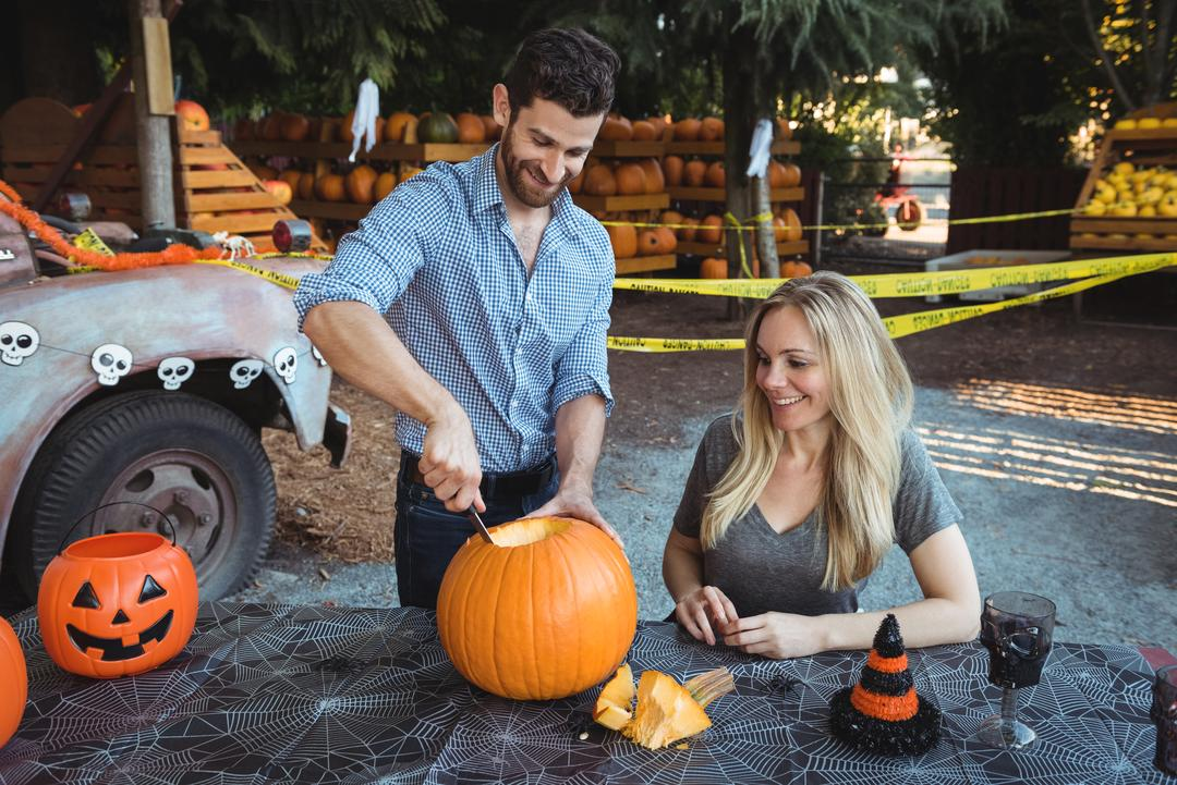 Couple preparing halloween while having a glass of wine