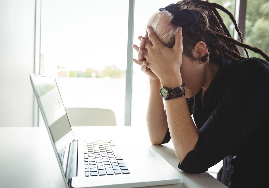 Image of a Stressed Looking Woman Using her Laptop