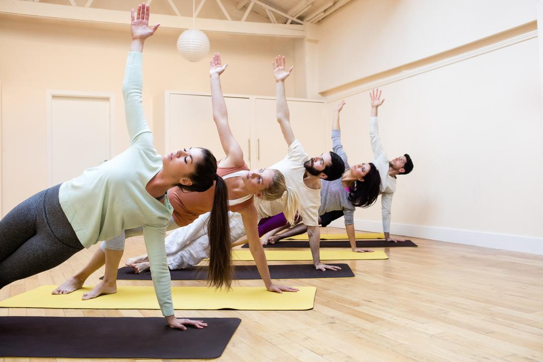 Group of people performing stretching exercise on exercise mat in the fitness studio Free Stock Images from PikWizard