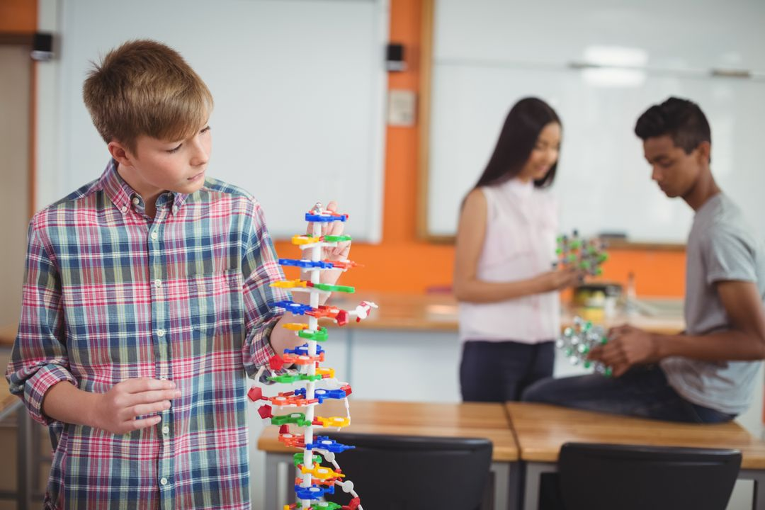 Schoolboy examining molecule model in laboratory at school Free Stock Images from PikWizard