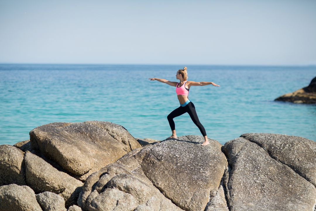 Full length of woman practicing warrior pose on rocky shore