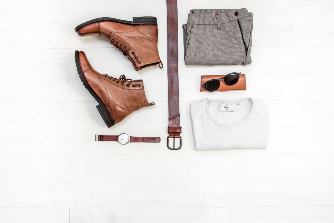 White Crew Neck Shirt Beside Black Sunglasses and Grey Slacks With Brown Leather Belt and Lace Up Boots