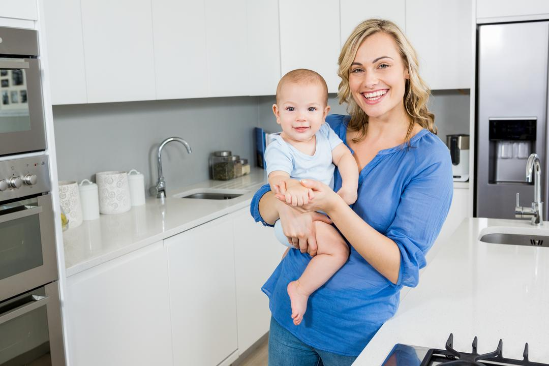 Portrait of mother holding her baby boy in kitchen at home Free Stock Images from PikWizard