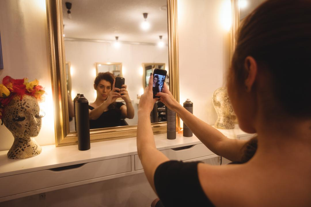 Woman taking selfie from mobile phone at saloon