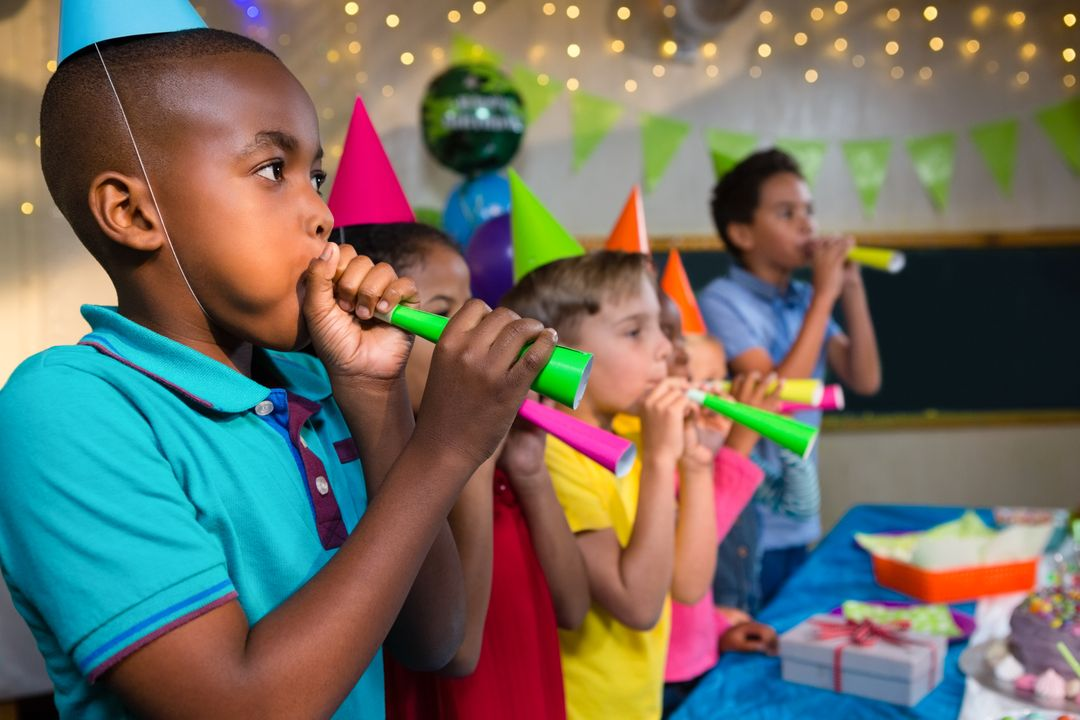 Children blowing party horns while standing by table during birthday party Free Stock Images from PikWizard