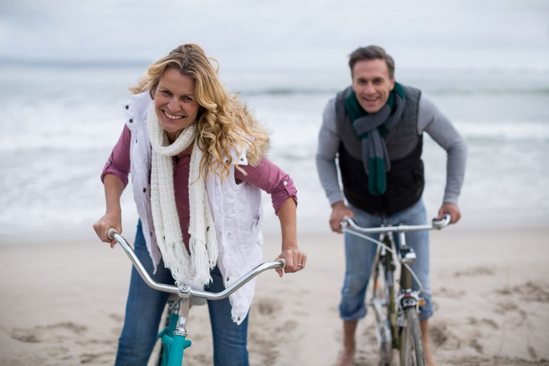 Portrait of mature couple riding bicycles on the beach  Free Stock Images from PikWizard