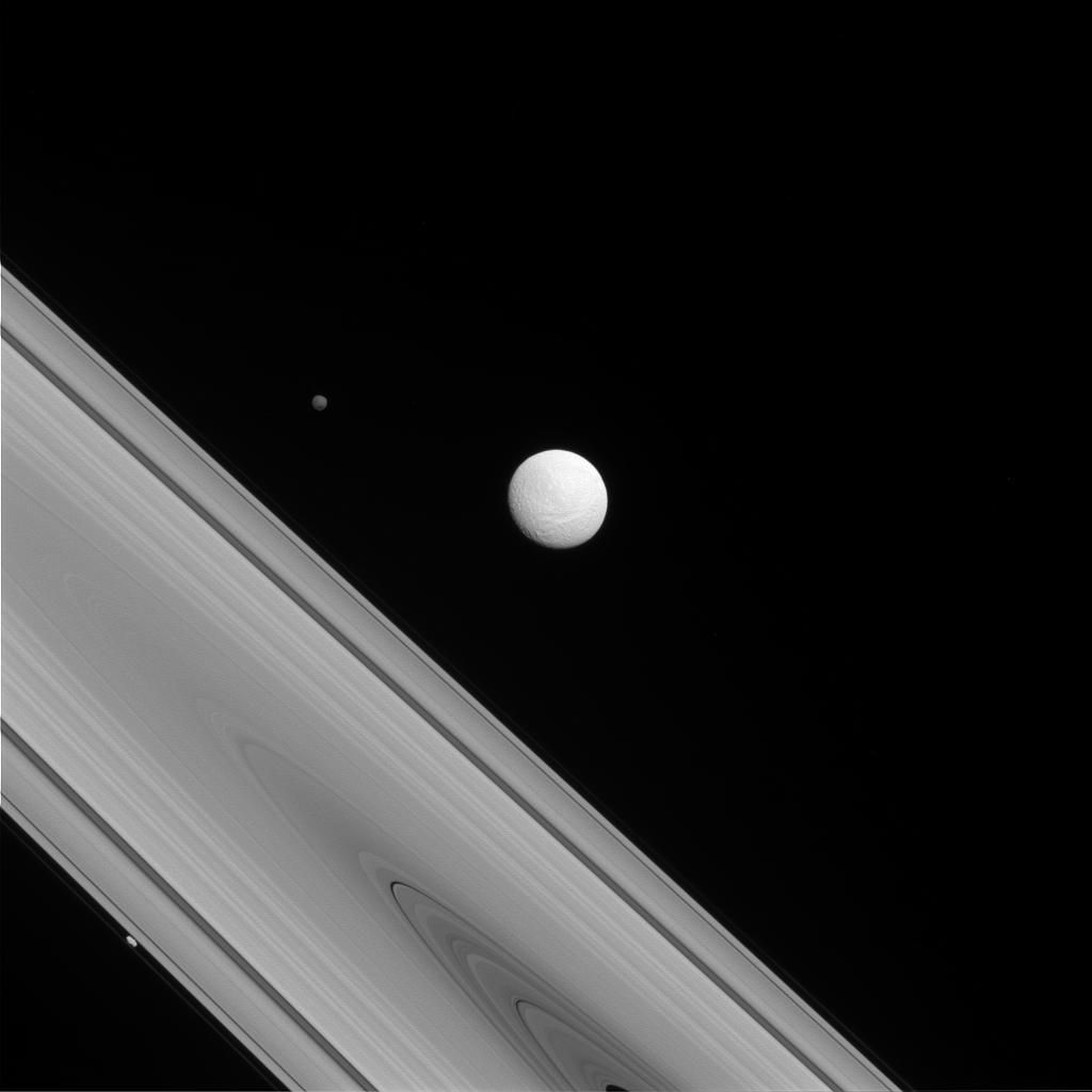 "The Cassini spacecraft captures a rare family photo of three of Saturn's moons that couldn't be more different from each other! As the largest of the three, Tethys (image center) is round and has a variety of terrains across its surface. Meanwhile, Hyperion (to the upper-left of Tethys) is the ""wild one"" with a chaotic spin and Prometheus (lower-left) is a tiny moon that busies itself sculpting the F ring.  To learn more about the surface of Tethys (660 miles, or 1,062 kilometers across), see PIA17164 More on the chaotic spin of Hyperion (168 miles, or 270 kilometers across) can be found at PIA07683 And discover more about the role of Prometheus (53 miles, or 86 kilometers across) in shaping the F ring in PIA12786.  This view looks toward the sunlit side of the rings from about 1 degree above the ringplane. The image was taken in visible light with the Cassini spacecraft narrow-angle camera on July 14, 2014.  The view was acquired at a distance of approximately 1.2 million miles (1.9 million kilometers) from Tethys and at a Sun-Tethys-spacecraft, or phase, angle of 22 degrees. Image scale is 7 miles (11 kilometers) per pixel.  http://photojournal.jpl.nasa.gov/catalog/PIA18283"