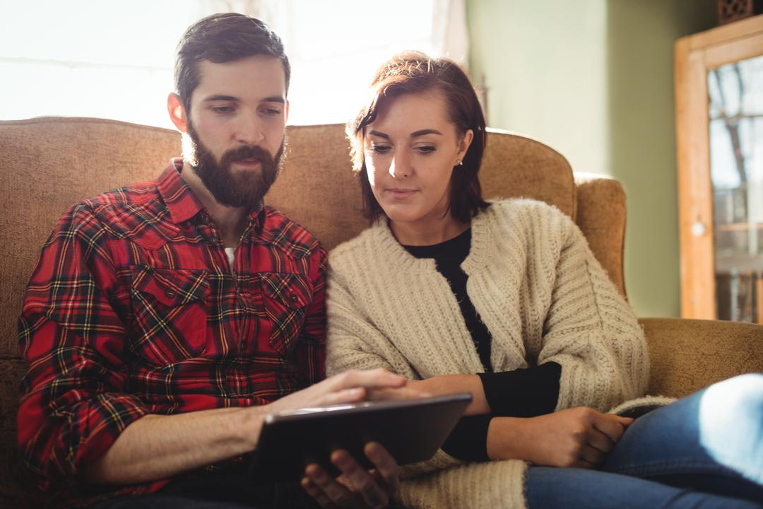 Couple using digital tablet in living room at home Free Stock Images from PikWizard