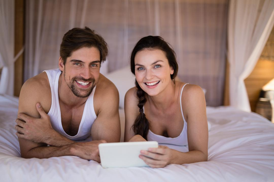 Portrait of smiling couple using digital tablet on bed in cottage