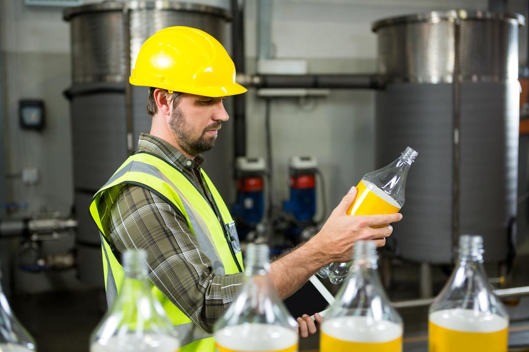 Side view of serious male worker inspecting bottles in juice factory
