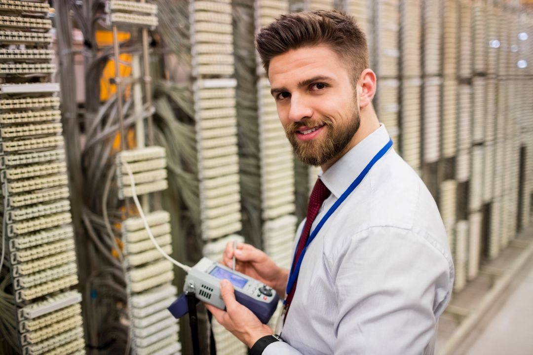 Portrait of technician using digital cable analyzer in server room Free Stock Images from PikWizard