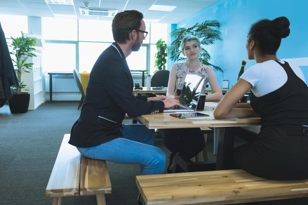 Executives having discussion at table in office
