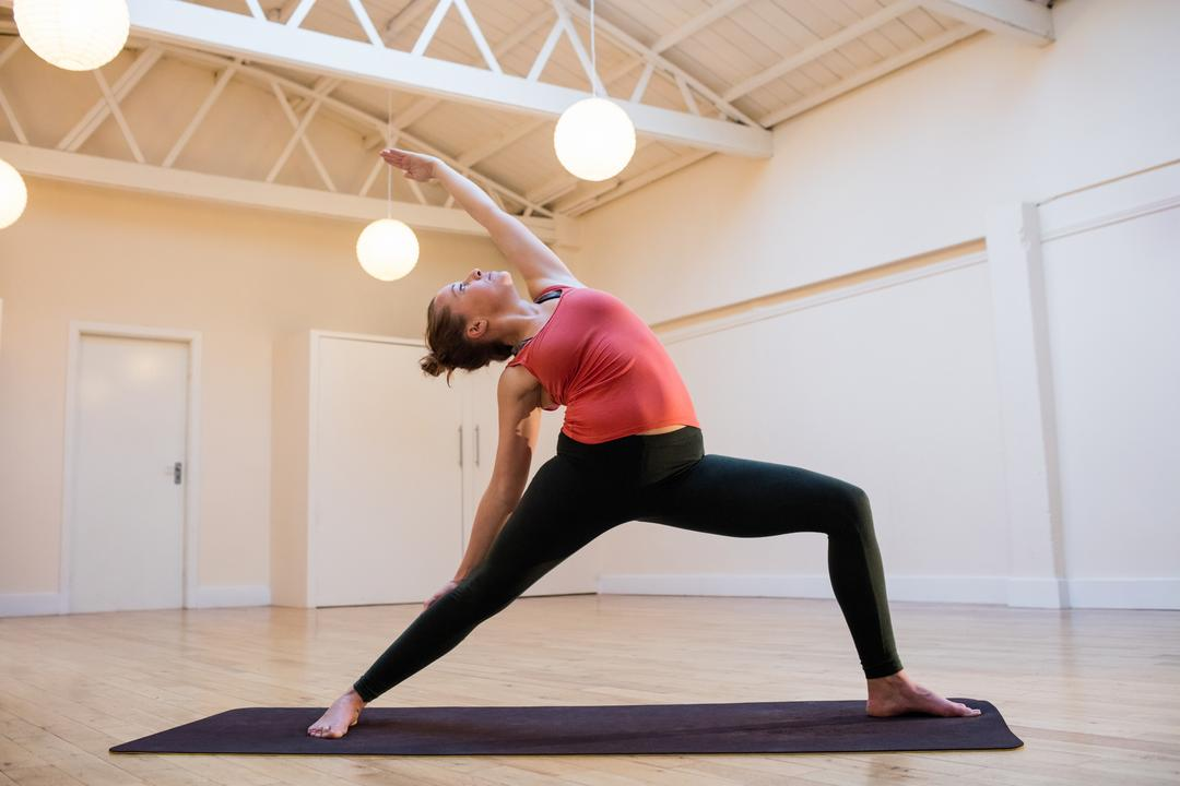 Woman performing triangle pose on exercise mat in fitness studio