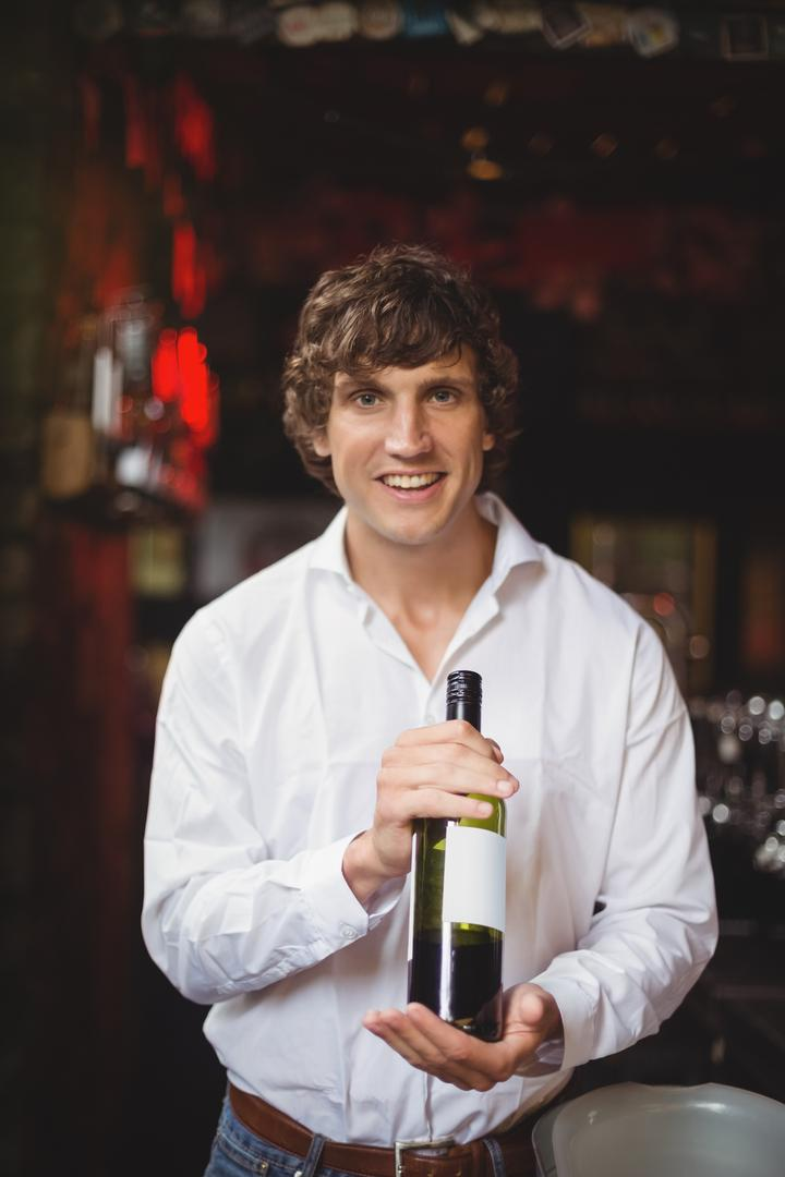 Portrait of bar tender holding a bottle of wine at bar Free Stock Images from PikWizard
