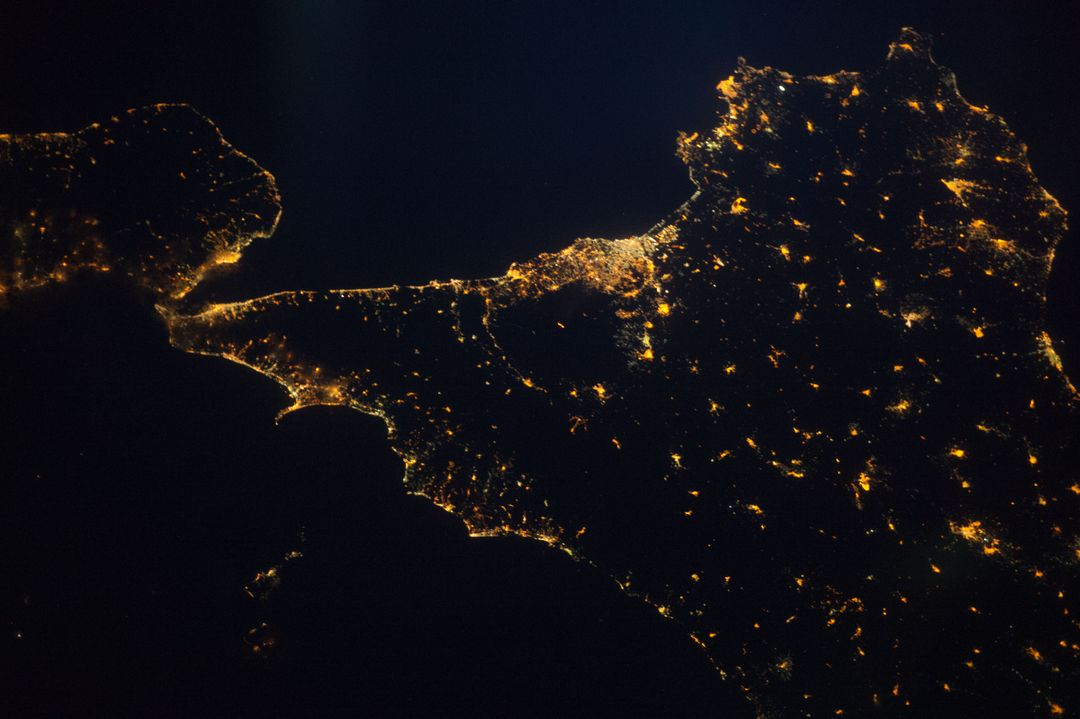 "ISS040-E-087282 (1 Aug. 2014) --- The Italian island/province of Sicily is almost totally visible in this nighttime nadir image photographed from 221 nautical miles above Earth by one of the Expedition 40 crew members aboard the International Space Station. The ""toe"" of Italy's ""boot"" is in the upper left corner."
