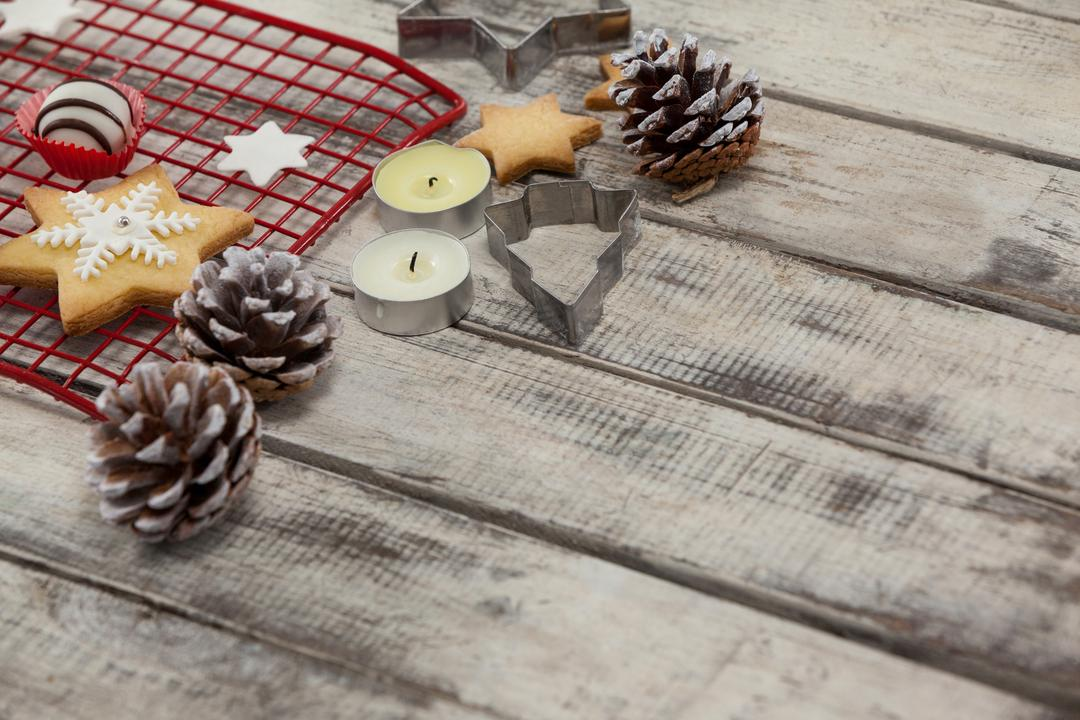 Cookie cutters with pine cone and tealight candles on a plank