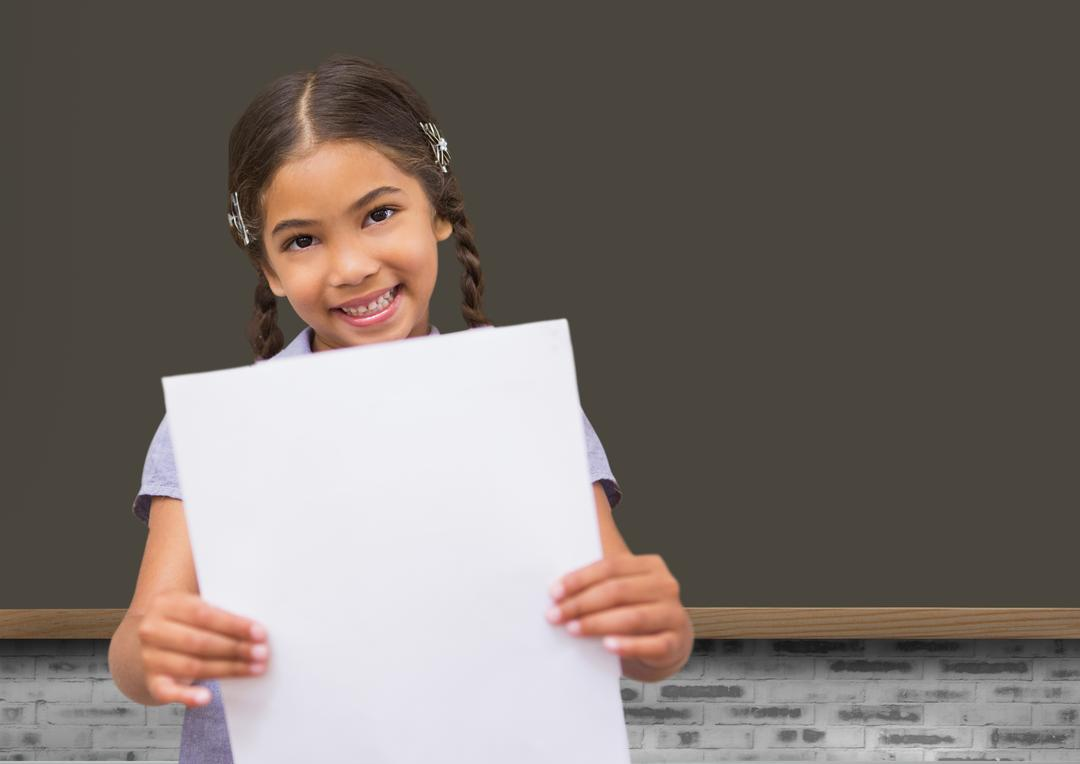 Smiling school girl holding blank paper against blackboard in background Free Stock Images from PikWizard
