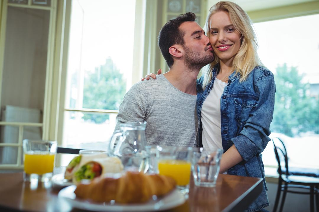 Smiling man kissing on woman cheeks in café