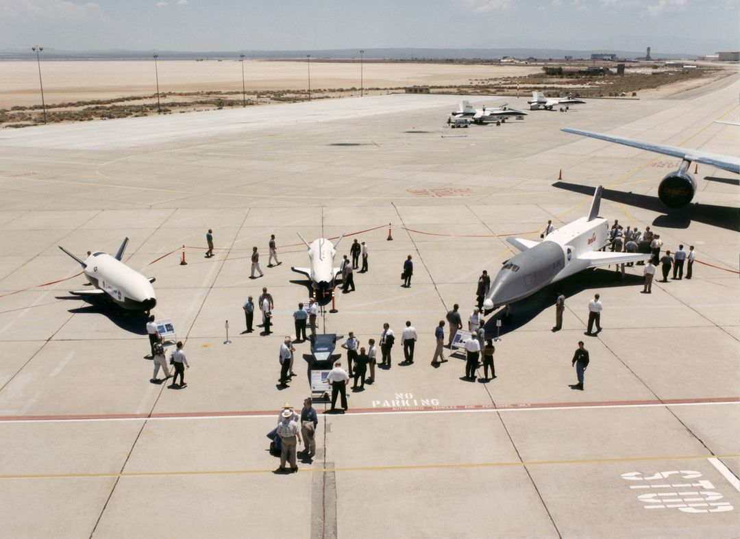 Aerospace industry representatives view actual and mock-up versions of 'X-Planes' intended to enhance access to space during a technical exposition on June 22, 2000 at Dryden Flight Research Center, Edwards, California. From left to right: NASA's B-52 launch aircraft, in service with NASA since 1959; a neutral-buoyancy model of the Boeing's X-37; the Boeing X-40A behind the MicroCraft X-43 mock-up; Orbital Science's X-34 and the modified Lockheed L-1011 airliner that was intended to launch the X-34. These X-vehicles are part of NASA's Access to Space plan intended to bring new technologies to bear in an effort to dramatically lower the cost of putting payloads in space, and near-space environments. The June 22, 2000 NASA Reusable Launch Vehicle (RLV) Technology Exposition included presentations on the history, present, and future of NASA's RLV program. Special Sessions for industry representatives highlighted the X-37 project and its related technologies. The X-37 project is managed by NASA's Marshall Space Flight Center, Huntsville, Alabama.