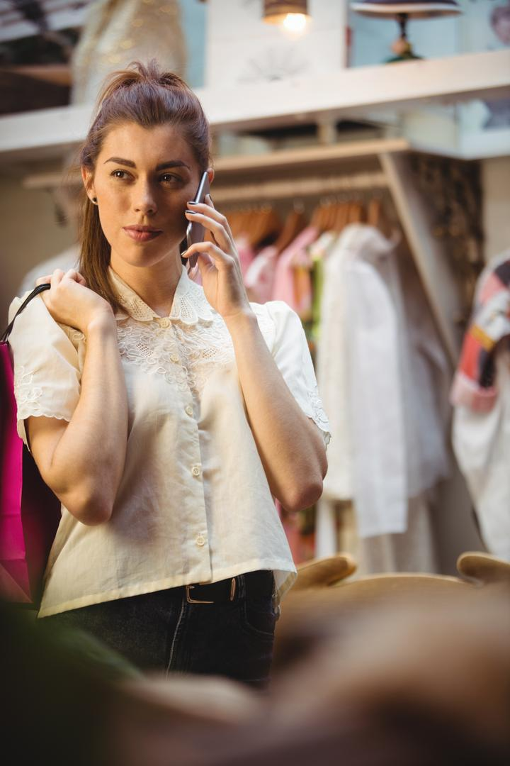 Woman talking on mobile phone while shopping in boutique store