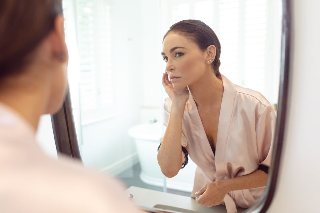 Beautiful woman looking at her face in the mirror at bathroom