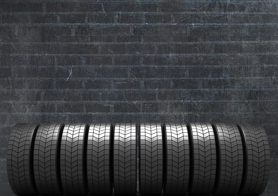Digital composition of stack of tyres against black brick background