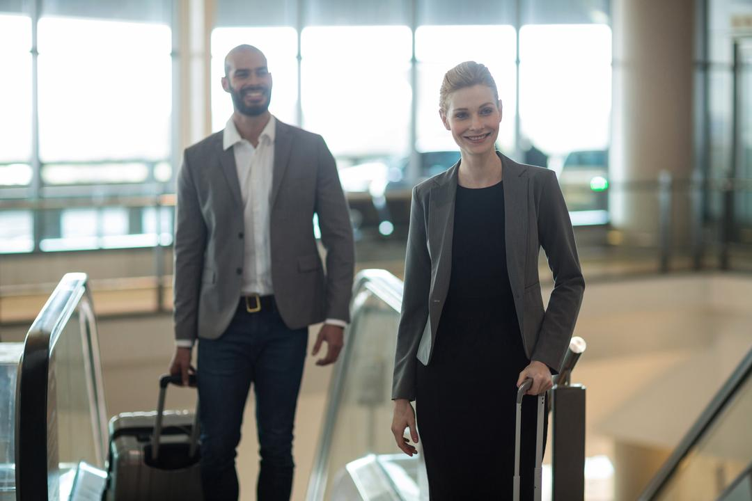 Smiling businesspeople with luggage standing in front of an escalator at airport terminal