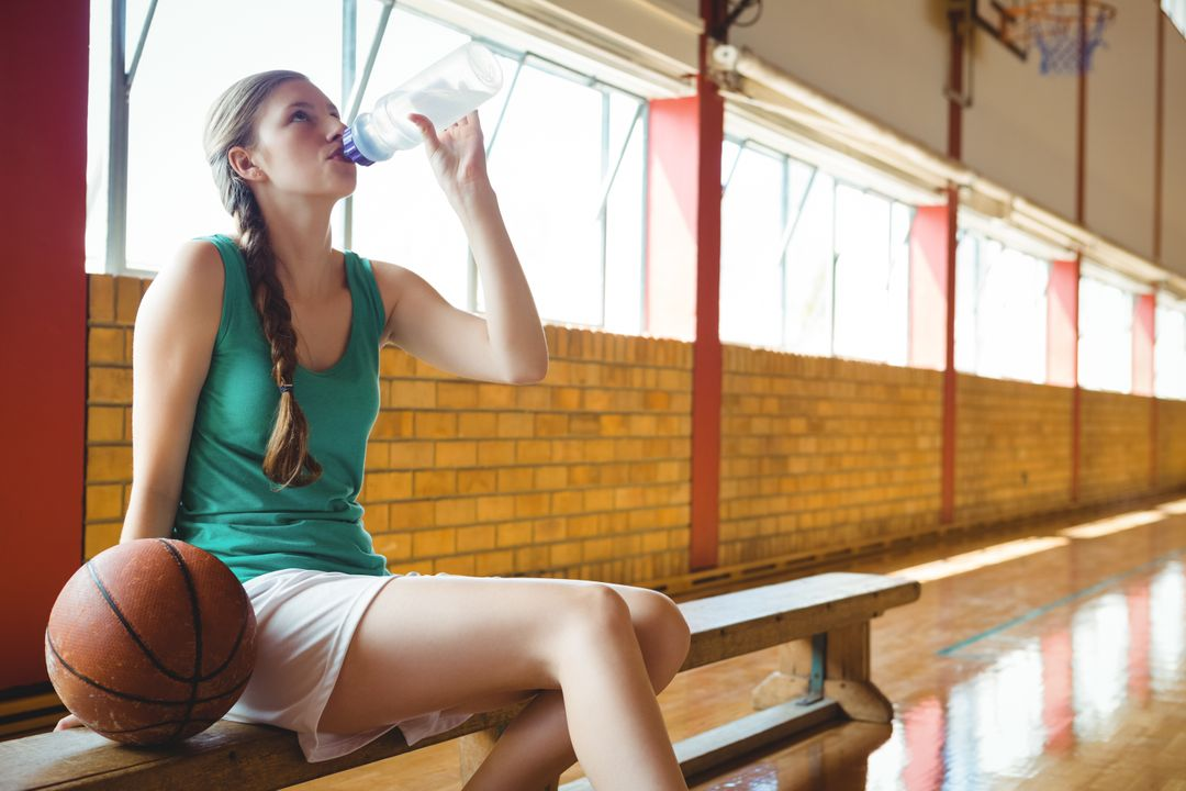 Woman drinking water while sitting on bench in court Free Stock Images from PikWizard