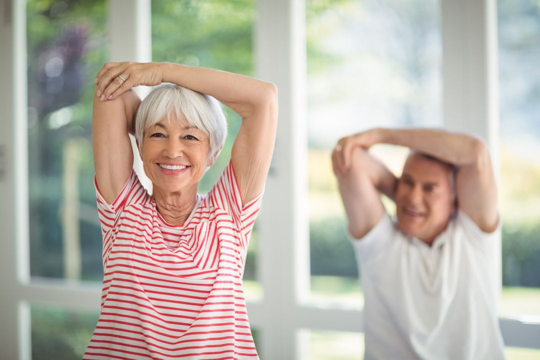 Elderly couple stretching in their living room for fitness blog