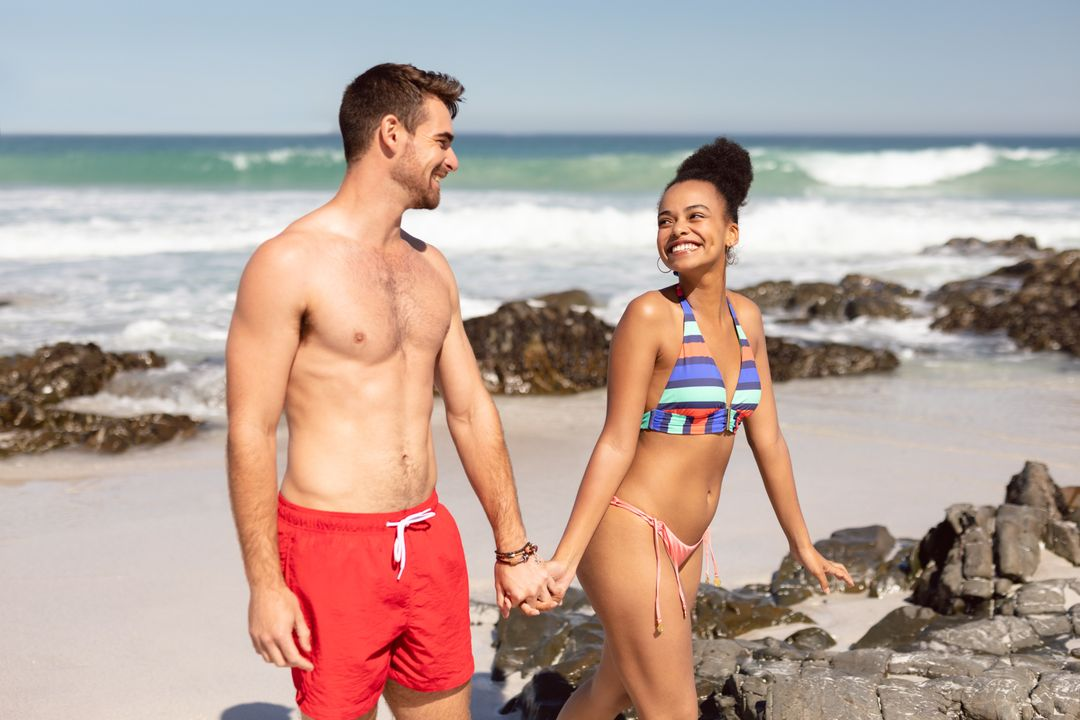 Front view of happy young diverse couple holding hands and walking on beach in the sunshine