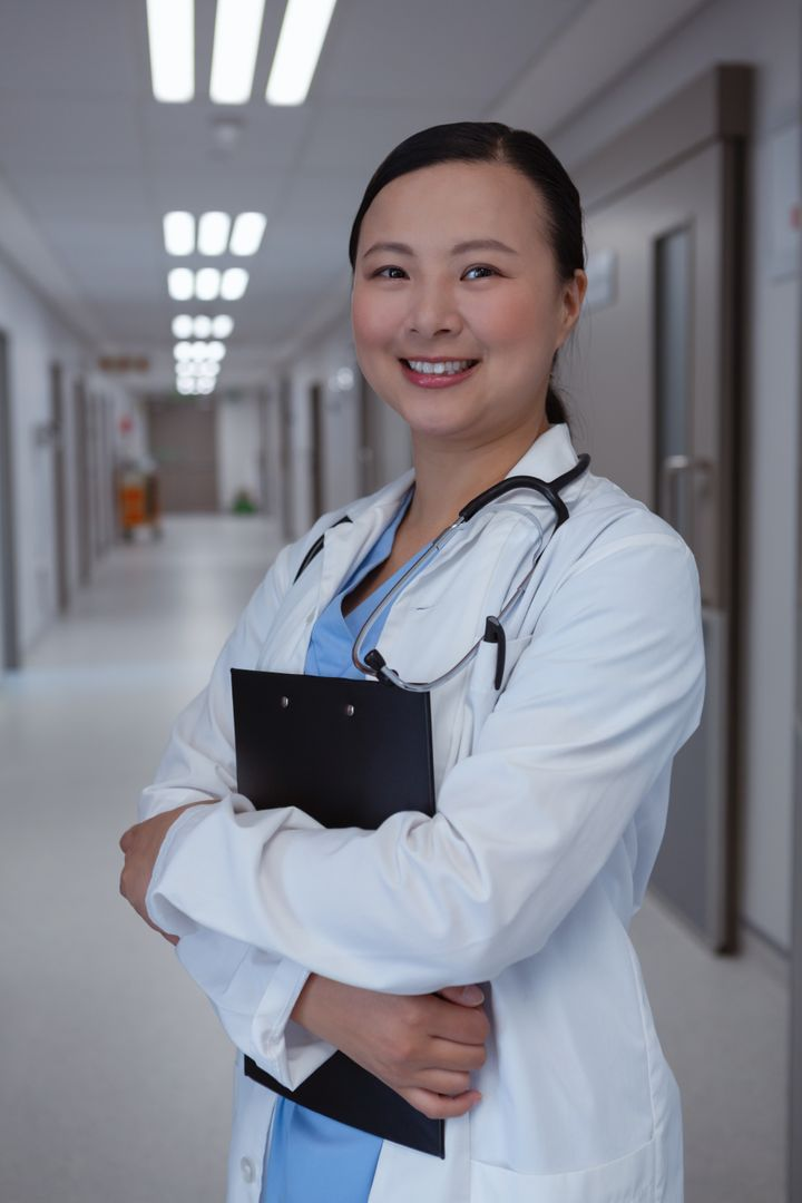 Front view of happy female doctor standing with clipboard in corridor at hospital