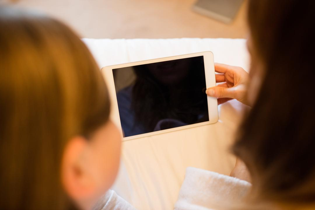 Mother and daughter using digital tablet in bedroom at home