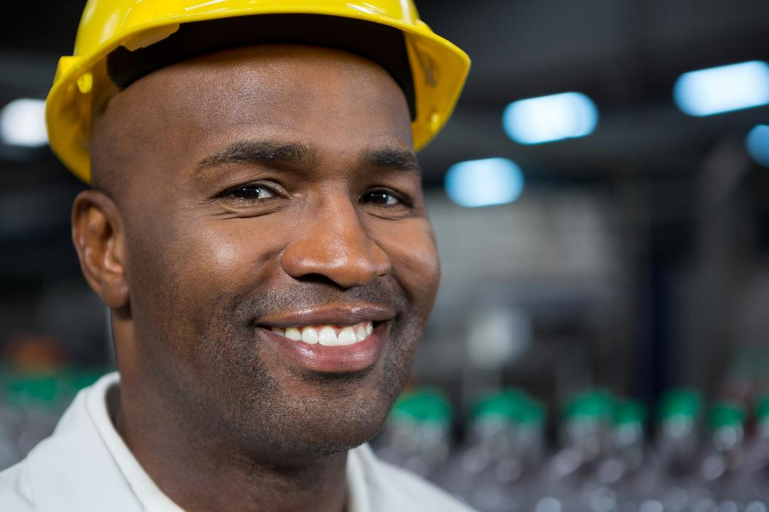 Close up portrait of smiling male worker wearing hard hat in warehouse