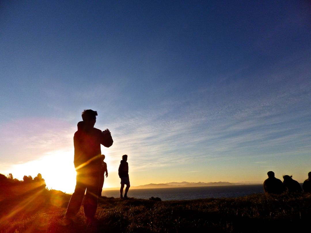 People on a hill during sunset
