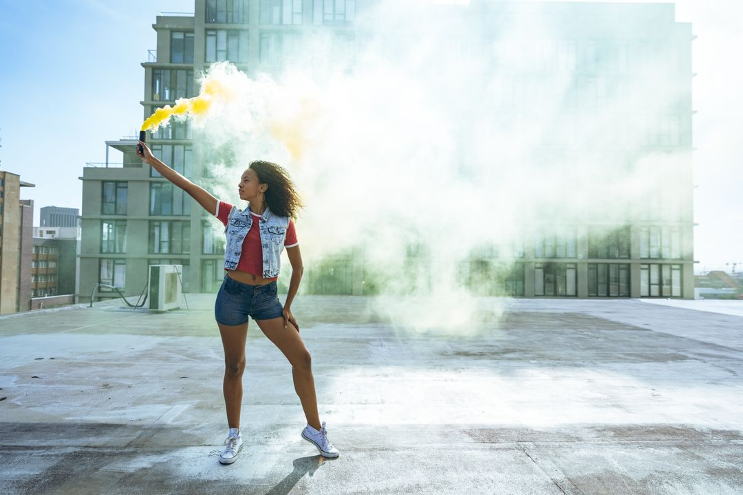 Front view of a hip young mixed race woman wearing denim jacket and jeans, holding a smoke grenade with yellow smoke on an urban rooftop with building in the background. Free Stock Images from PikWizard